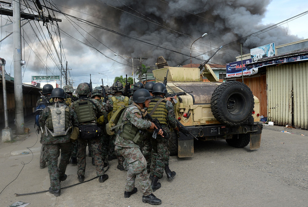 Description of . Members of the Philippine national police special forces take cover as they move forward to enemy positions among burning houses during a fire fight with Muslim rebels, as a stand-off entered its fourth day in Zamboanga City on the southern island of Mindanao on September 12, 2013.   AFP PHOTO/TED ALJIBE/AFP/Getty Images