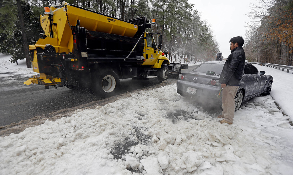 Description of . Julian Ramirez watches a snow plow as he waits to dig his car from the frozen roadside after abandoning the vehicle overnight during the storm in Chapel Hill, N.C., Thursday, Feb. 13, 2014. The National Weather Service issued a winter storm warning lasting into Thursday covering 95 of the state\'s 100 counties. (AP Photo/Gerry Broome)