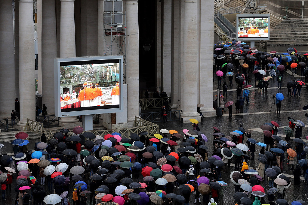 Description of . People gather in St Peter\'s Square to watch large screens displaying live footage from inside the Sistine Chapel as Cardinals prepare for the first day of the conclave on March 12, 2013 in Vatican City, Vatican. (Photo by Joe Raedle/Getty Images)