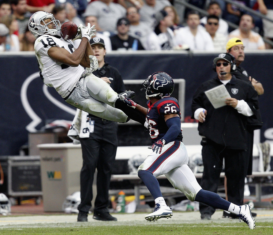 Description of . Andre Holmes #18 of the Oakland Raiders makes a catch as he beats Brandon Harris #26 of the Houston Texans on the play in the thrid quarter at Reliant Stadium on November 17, 2013 in Houston, Texas. The play was reviewed and ruled incomplete.  (Photo by Bob Levey/Getty Images)