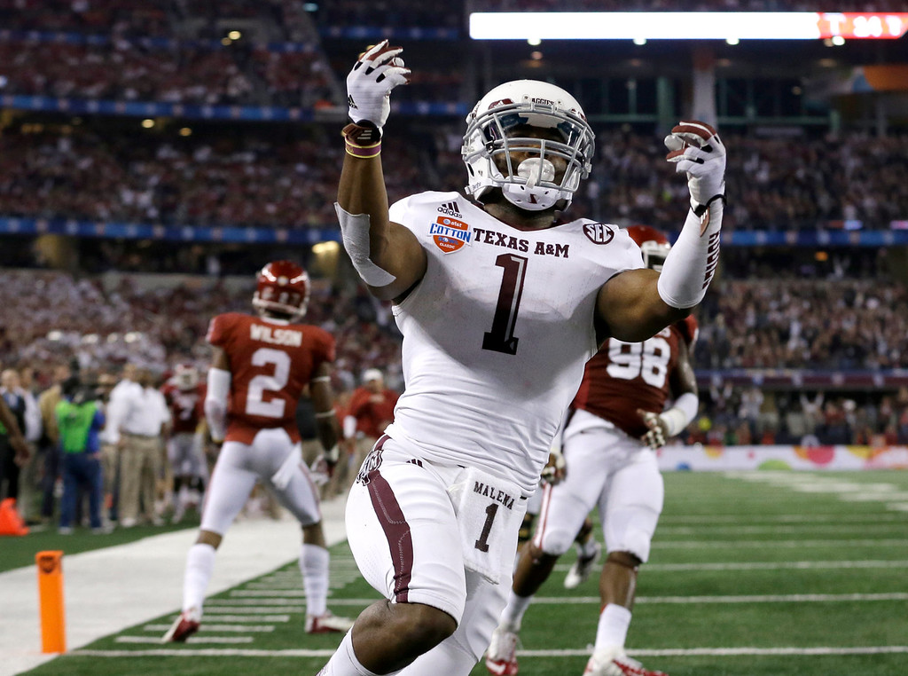 Description of . Texas A&M's Ben Malena (1) celebrates his touchdown as Oklahoma's Julian Wilson (2) and Chuka Ndulue (98) walk away in the second half of the Cotton Bowl NCAA college football game Friday, Jan. 4, 2013, in Arlington, Texas. (AP Photo/LM Otero)