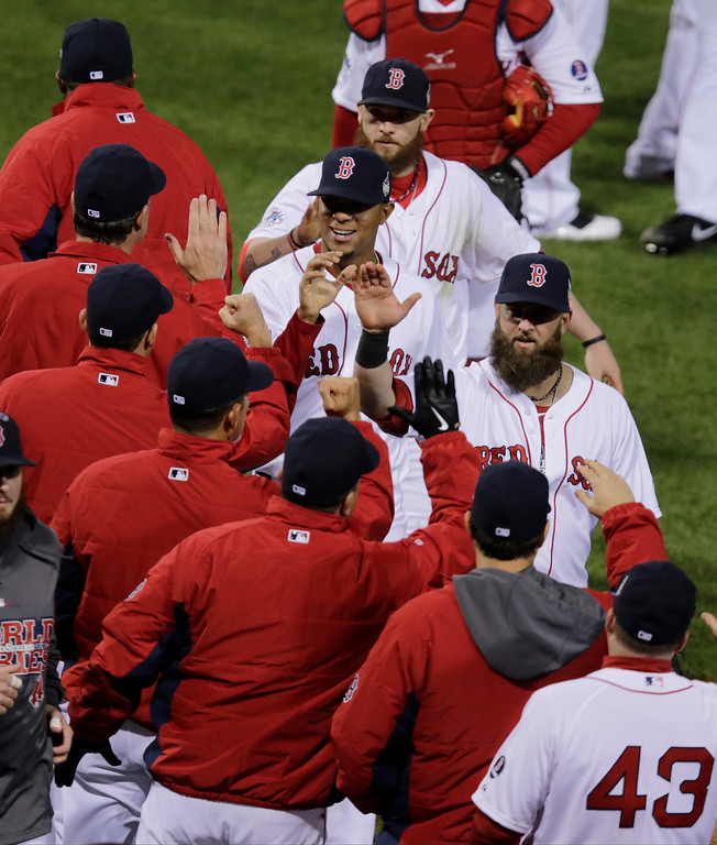 Description of . Boston Red Sox players celebrate after Game 1 of baseball's World Series against the St. Louis Cardinals Wednesday, Oct. 23, 2013, in Boston. The Red Sox won 8-1 to take a 1-0 lead in the series. (AP Photo/Charles Krupa)
