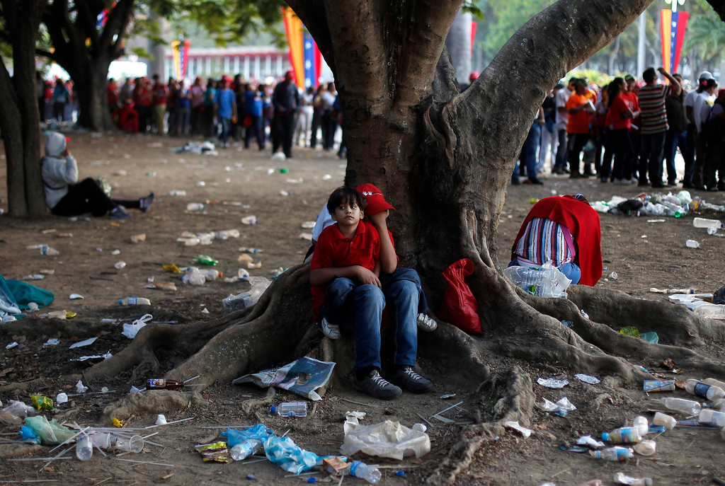 Description of . Supporters of Venezuela's late President Hugo Chavez sit at a tree as they wait for a chance to view his body lying in state, at the military academy in Caracas March 8, 2013.         REUTERS/Tomas Bravo