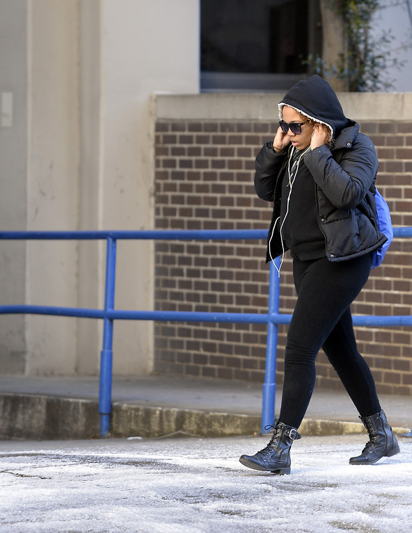 . A pedestrian bundles up and crosses an icy patch on the sidewalk at Georgia State University as a cold Arctic blast brought temperatures down to 6 degrees above zero to shatter cold weather records, on Tuesday, Jan. 7, 2014, in Atlanta. (AP Photo/David Tulis)