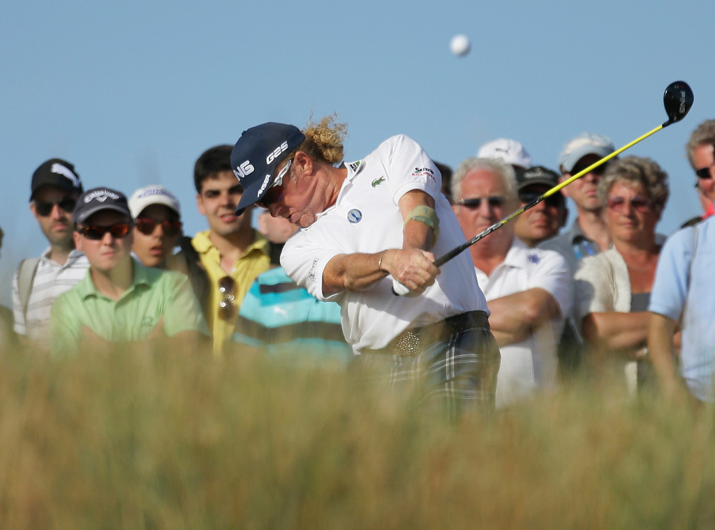 Description of . Miguel Angel Jimenez of Spain plays a shot off the 14th tee during the third round of the British Open Golf Championship at Muirfield, Scotland, Saturday July 20, 2013. (AP Photo/Jon Super)
