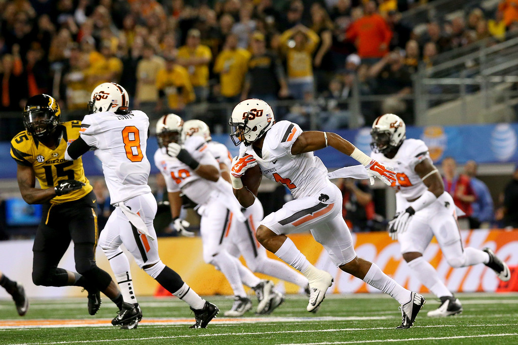 Description of . ARLINGTON, TX - JANUARY 03:  Justin Gilbert #4 of the Oklahoma State Cowboys intercepts a pass in the first quarter against the Missouri Tigers during the AT&T Cotton Bowl on January 3, 2014 in Arlington, Texas.  (Photo by Ronald Martinez/Getty Images)
