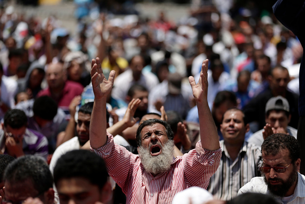Description of . Supporters of ousted Egyptian President Mohammed Morsi pray during the Friday prayer before a protest near the University of Cairo, Giza, Egypt, Friday, July 5, 2013. Tens of thousands, mainly Islamists, chanted