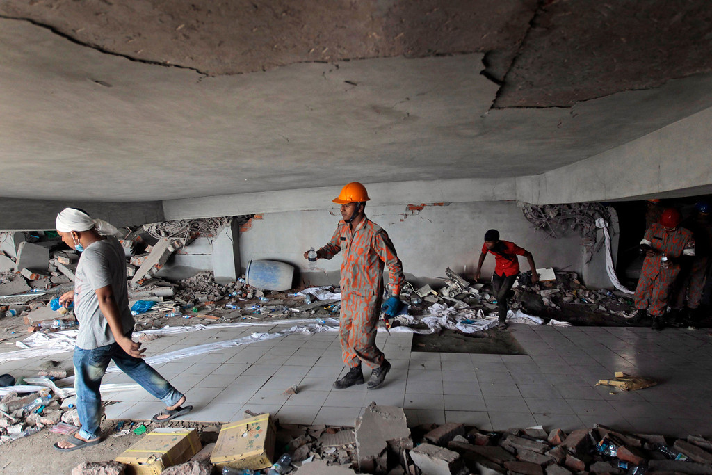 Description of . Bangladeshi rescuers work at the site of a building that collapsed Wednesday in Savar, near Dhaka, Bangladesh,Thursday, April 25, 2013. (AP Photo/A.M.Ahad)