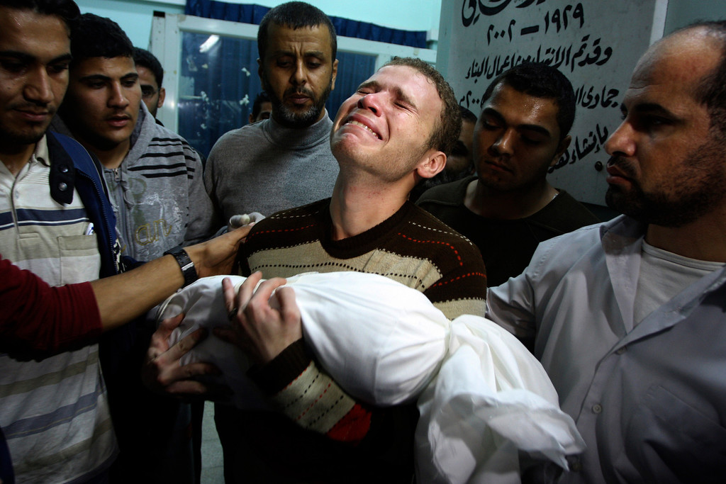 Description of . In this Nov. 14, 2012 file photo, Jihad Masharawi weeps while he holds the body of his 11-month old son Ahmad, at Shifa hospital following an Israeli air strike on their family house, in Gaza City. The Israeli military said its assassination of the Hamas military commander Ahmed Jabari, marks the beginning of an operation against Gaza militants. (AP Photo/Majed Hamdan, File)