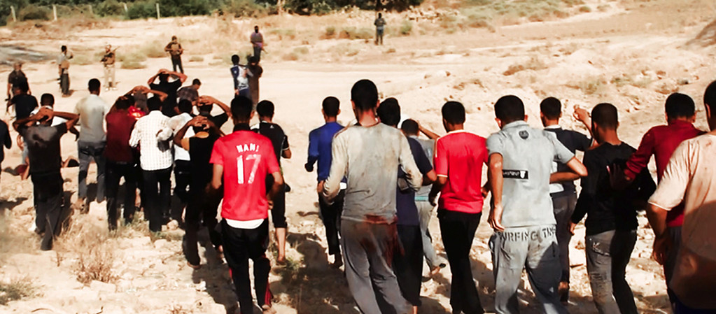 Description of . This image posted on a militant website on Saturday, June 14, 2014, which has been verified and is consistent with other AP reporting, appears to show militants from the al-Qaida-inspired Islamic State of Iraq and the Levant (ISIL) leading captured Iraqi soldiers wearing plain clothes to an open field moments before shooting them in Tikrit, Iraq. The Islamic militant group that seized much of northern Iraq has posted photos that appear to show its fighters shooting dead dozens of captured Iraqi soldiers in a province north of the capital Baghdad. Iraq's top military spokesman Lt. Gen. Qassim al-Moussawi confirmed the photosí authenticity on Sunday and said he was aware of cases of mass murder of Iraqi soldiers. (AP Photo via militant website)