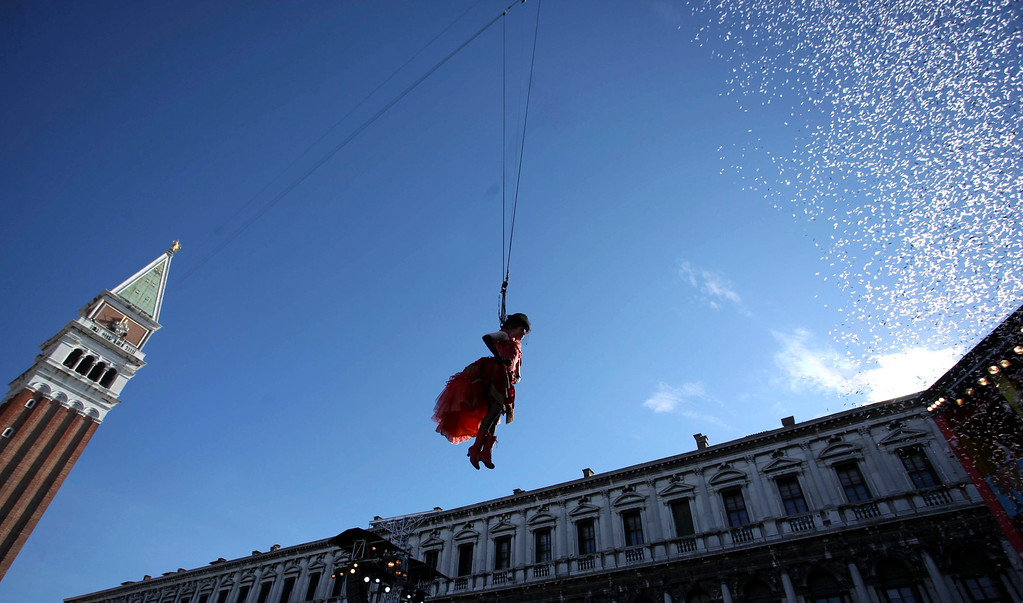 Description of . The traditional Columbine descends from Saint Mark's bell tower on an iron cable during the Venetian Carnival in Venice February 3, 2013.  REUTERS/Manuel Silvestri