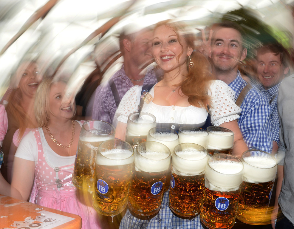 Description of . A waitress serves beer mugs during the opening of the Oktoberfest beer festival at the Theresienwiese in Munich, southern Germany, on September 21, 2013. The world's biggest beer festival Oktoberfest will run until October 6, 2013.  AFP PHOTO / CHRISTOF  STACHE/AFP/Getty Images