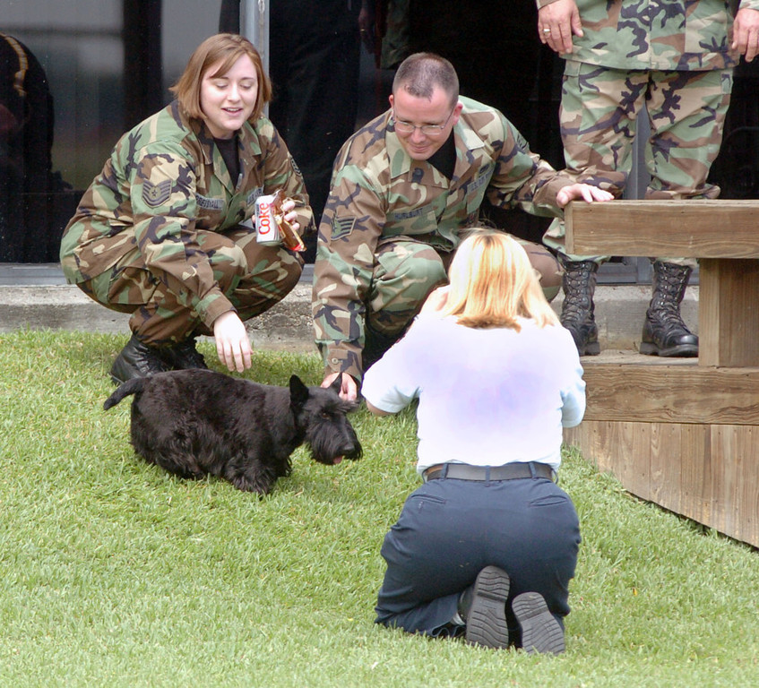 Description of . Texas Air National Guardsmen, Tech Sgt. Shannon Pressnall, left, and Staff Sgt. Lyle L. Hurlburt, second left, play with Barney, President Bush's dog, as Jane Hatch, a registered nurse from Galvestion, Texas, back to camera, takes their picture, Tuesday, April 26, 2005, at Ellington Field in Houston. The dog stayed at Ellington Field as the president attended a forum on Social Security in Galveston. (AP Photo/Tim Johnson)