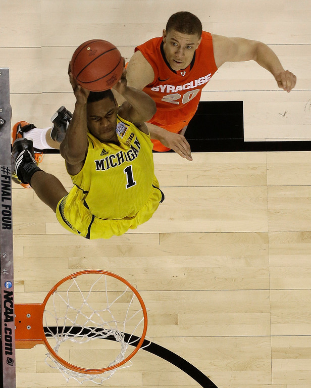 Description of . Michigan's Glenn Robinson III (1) heads to the hoop as Syracuse's Brandon Triche (20) defends during the second half of the NCAA Final Four tournament college basketball semifinal game Saturday, April 6, 2013, in Atlanta. (AP Photo/Charlie Neibergall)