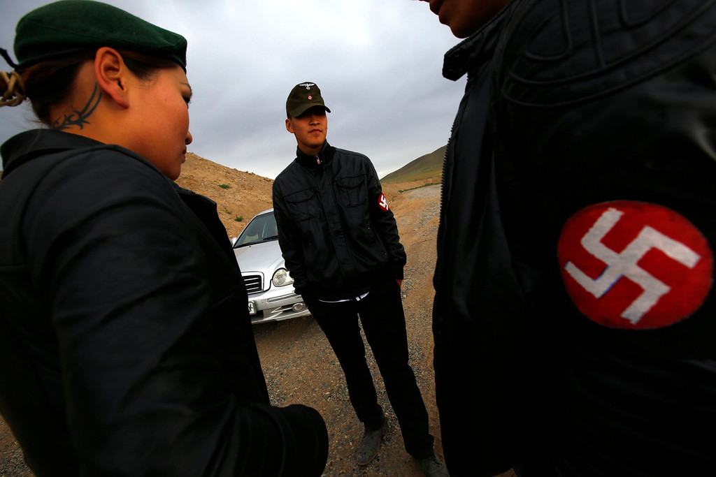 Description of . Members of the Mongolian neo-Nazi group Tsagaan Khass stand near a quarry, where they questioned a worker, southwest of Ulan Bator June 23, 2013. The group has rebranded itself as an environmentalist organisation fighting pollution by foreign-owned mines, seeking legitimacy as it sends Swastika-wearing members to check mining permits. Over the past years, ultra-nationalist groups have expanded in the country and among those garnering attention is Tsagaan Khass, which has recently shifted its focus from activities such as attacks on women it accuses of consorting with foreign men to environmental issues, with the stated goal of protecting Mongolia from foreign mining interests. This ultra-nationalist group was founded in the 1990s and currently has 100-plus members. Picture taken June 23, 2013. REUTERS/Carlos Barria