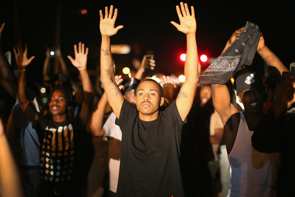 Description of . FERGUSON, MO - AUGUST 12:  Demonstrators protest the killing of teenager Michael Brown on August 12, 2014 in Ferguson, Missouri. Brown was shot and killed by a police officer on Saturday in the St. Louis suburb of Ferguson. Ferguson has experienced two days of violent protests since the killing but, tonight\'s protest was peaceful.  (Photo by Scott Olson/Getty Images)