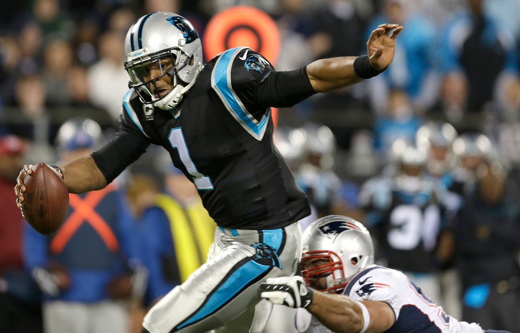 . Carolina Panthers\' Cam Newton (1) avoids a sack by a New England Patriots defender during the second half of an NFL football game in Charlotte, N.C., Monday, Nov. 18, 2013. (AP Photo/Bob Leverone)