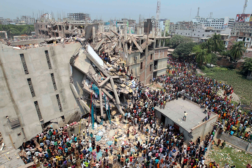 Description of . People and rescuers gather after an eight-story building housing several garment factories collapsed in Savar, near Dhaka, Bangladesh, Wednesday, April 24, 2013. Dozens were killed and many more are feared trapped in the rubble. (AP Photo/ A.M. Ahad)