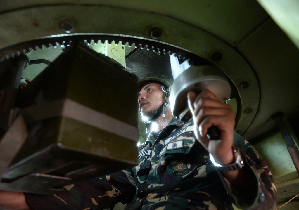 Description of . A Philippine soldier mans a machine gun inside an armored personnel carrier during a fire fight between government forces and Muslim rebels as stand-off entered its fourth day in Zamboanga City on the southern island of Mindanao on September 12, 2013.  AFP PHOTO/TED ALJIBE/AFP/Getty Images