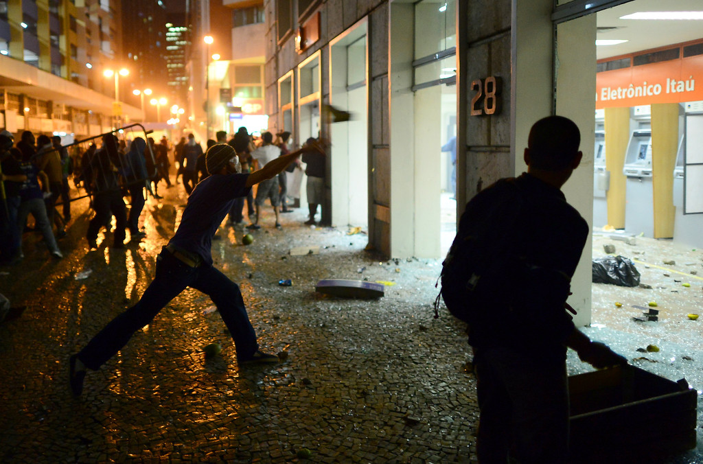 Description of . Demonstrators cause destruction in downtown Rio de Janeiro on June 17, 2013, after a protest against higher public transportation fares and the use of public funds to finance international football tournaments. Protesters in several major cities are up in arms over hikes in mass transit prices -- from $1.5 to $1.6 -- as well as over the $15 billion earmarked for the two sports events amid calls for more health and education funding.   CHRISTOPHE SIMON/AFP/Getty Images