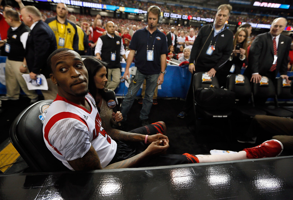 Description of . ATLANTA, GA - APRIL 06:  Injured Louisville Cardinals player Kevin Ware #5 sits on the bench as he waits to be interviewed by CBS Sports reporter Tracy Wolfson before the Cardinals take on the Wichita State Shockers in the 2013 NCAA Men's Final Four Semifinal at the Georgia Dome on April 6, 2013 in Atlanta, Georgia.  (Photo by Kevin C. Cox/Getty Images)
