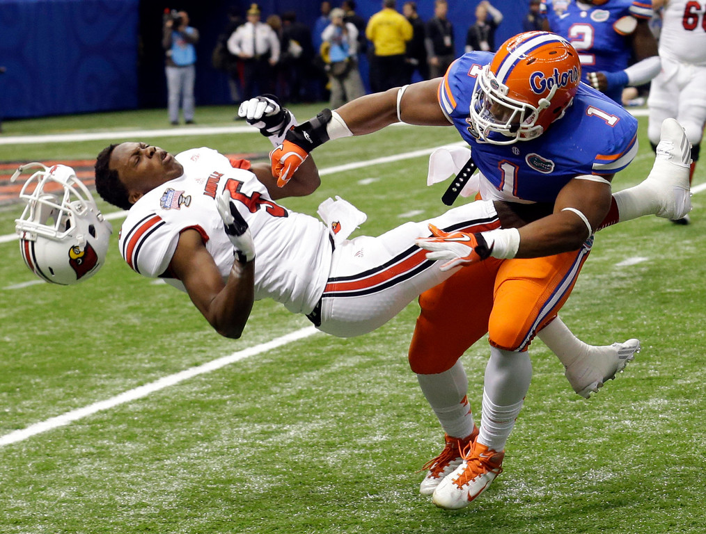 Description of . Florida linebacker Jon Bostic (1) hits Louisville quarterback Teddy Bridgewater (5) hard enough to dislodge his helmet in the first quarter of the Sugar Bowl NCAA college football game Wednesday, Jan. 2, 2013, in New Orleans. (AP Photo/Bill Haber)
