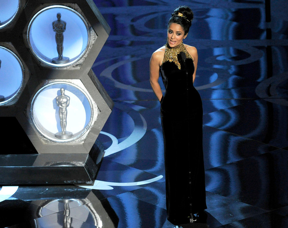 Description of . Actress Salma Hayek speaks on stage during the Oscars at the Dolby Theatre on Sunday Feb. 24, 2013, in Los Angeles.  (Photo by Chris Pizzello/Invision/AP)