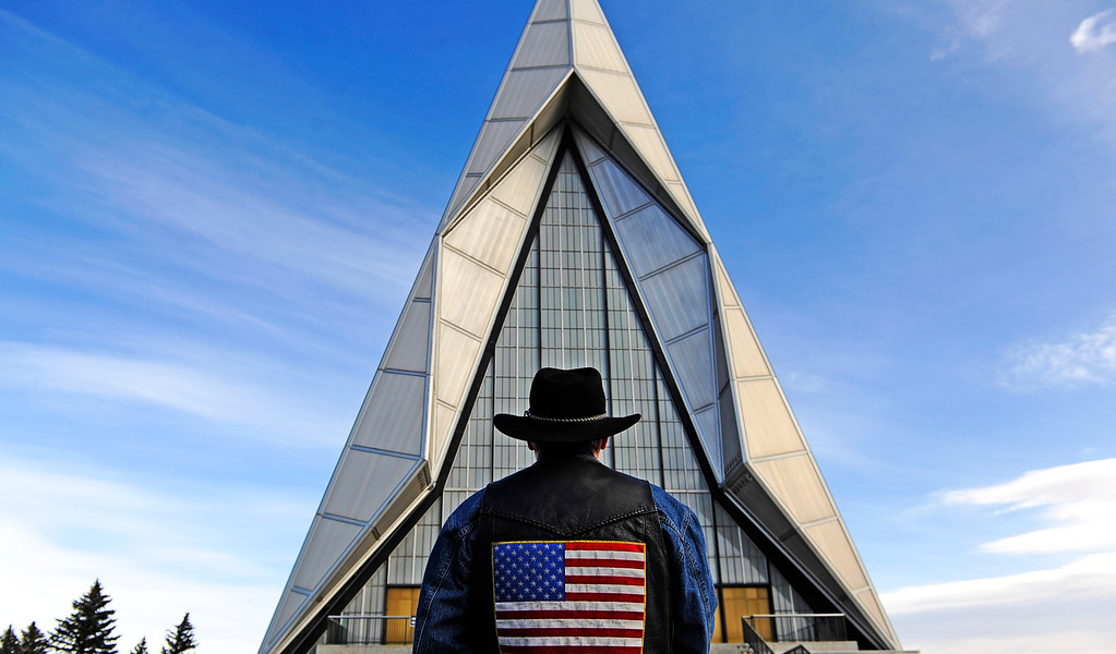Description of . Jay Hill, of Denver, a member of the Colorado Patriot Guard Riders, stands outside the Air Force Academy Cadet Chapel on Monday, March 12, 2012, during the funeral for Colorado native Capt. Ryan Hall. Hall was one of four Airmen killed Feb. 18 when his U-28 aircraft crashed near Camp Lemonnier, Djibouti, Africa. RJ Sangosti, The Denver Post