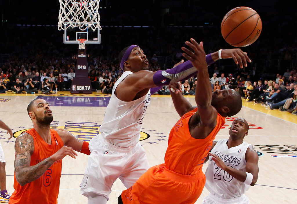 Description of . Los Angeles Lakers' Dwight Howard (2nd R) blocks a shot by New York Knicks' Raymond Felton as Knicks' Tyson Chandler (L) and Lakers' Jodie Meeks (R) look on during the second half of their NBA basketball game in Los Angeles December 25, 2012. REUTERS/Danny Moloshok