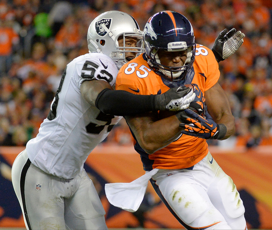 Description of . Denver Broncos tight end Virgil Green (85) is tackled by Oakland Raiders middle linebacker Nick Roach (53) in the third quarter. The Denver Broncos took on the Oakland Raiders at Sports Authority Field at Mile High in Denver on September 23, 2013. (Photo by John Leyba/The Denver Post)