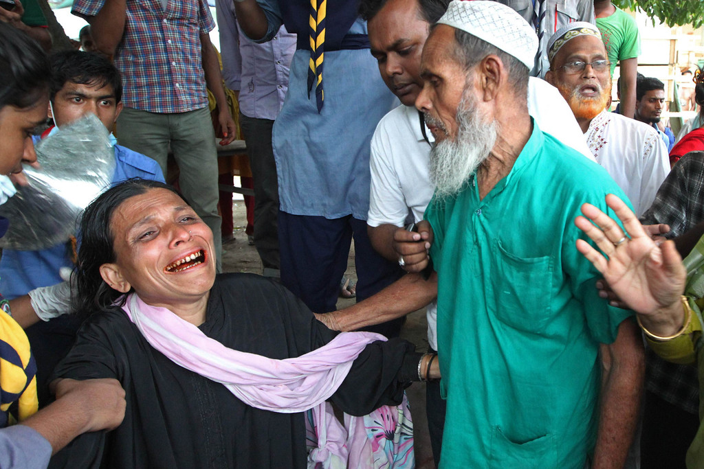 Description of . In this photograph taken  on April 29, 2013, the father (front L) and aunt (R) of Bangladeshi garment worker Shahina Akter react after her mortal remains were returned to the family following her unsuccessful rescue from the eight-story building that collapsed in Savar, on the outskirts of Dhaka.   AFP PHOTO/STR/FILESSTRDEL/AFP/Getty Images