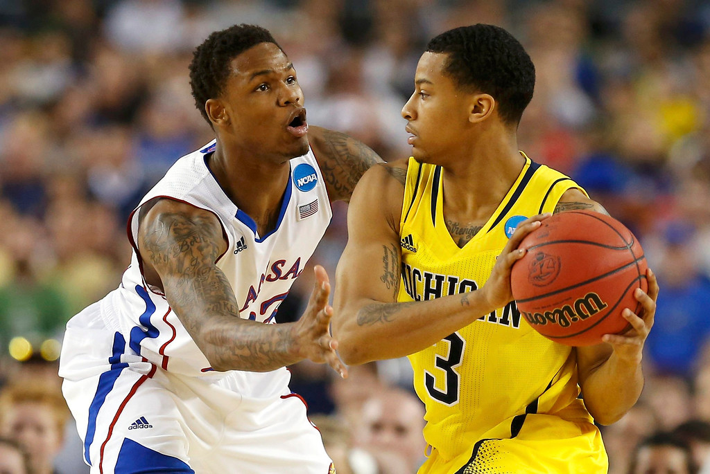 Description of . Kansas Jayhawks guard Ben McLemore (L) guards Michigan Wolverines guard Trey Burke during the first half in their South Regional NCAA mens basketball game in Arlington, Texas March 29, 2013. REUTERS/Jim Young