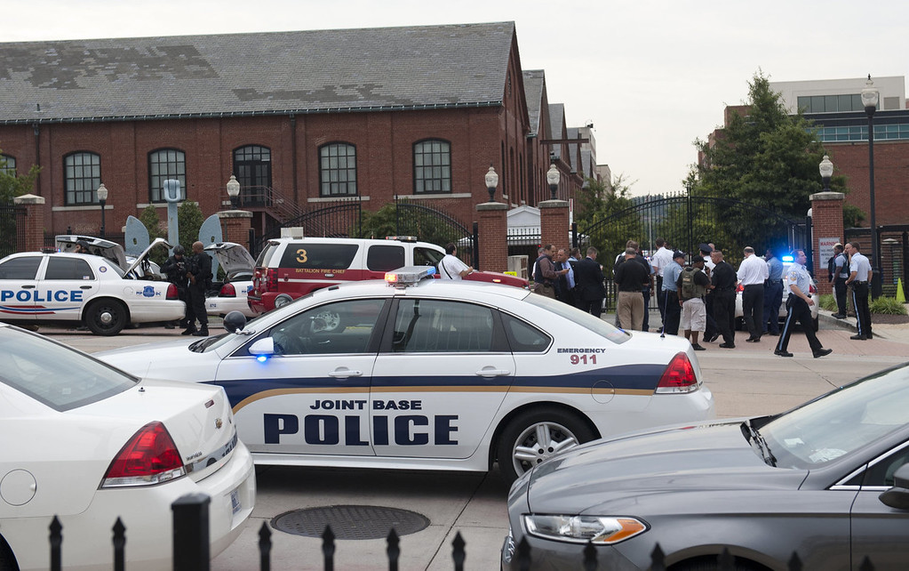 Description of . Police respond to the report of a shooting at the Navy Yard in Washington, DC, September 16, 2013.  A gunman shot and wounded at least one person Monday in a headquarters building at the US Navy Yard in Washington and is still at large, the navy said.