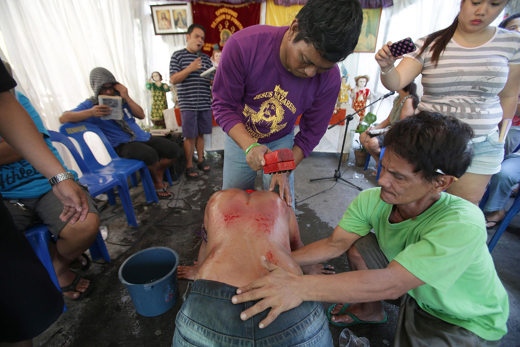 Description of . A man cuts small wounds on the back of a Filipino penitent during Maundy Thursday rituals to atone for sins on March 28, 2013, in suburban Mandaluyong, east of Manila, Philippines. The ritual is frowned upon by church leaders in this predominantly Roman Catholic country.  (AP Photo/Aaron Favila)