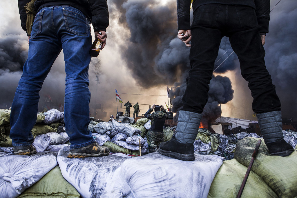 Description of . Anti-government demonstrators stand on barricades during clashes with riot police in Kiev on February 18, 2014.   AFP PHOTO / SANDRO MADDALENA/AFP/Getty Images