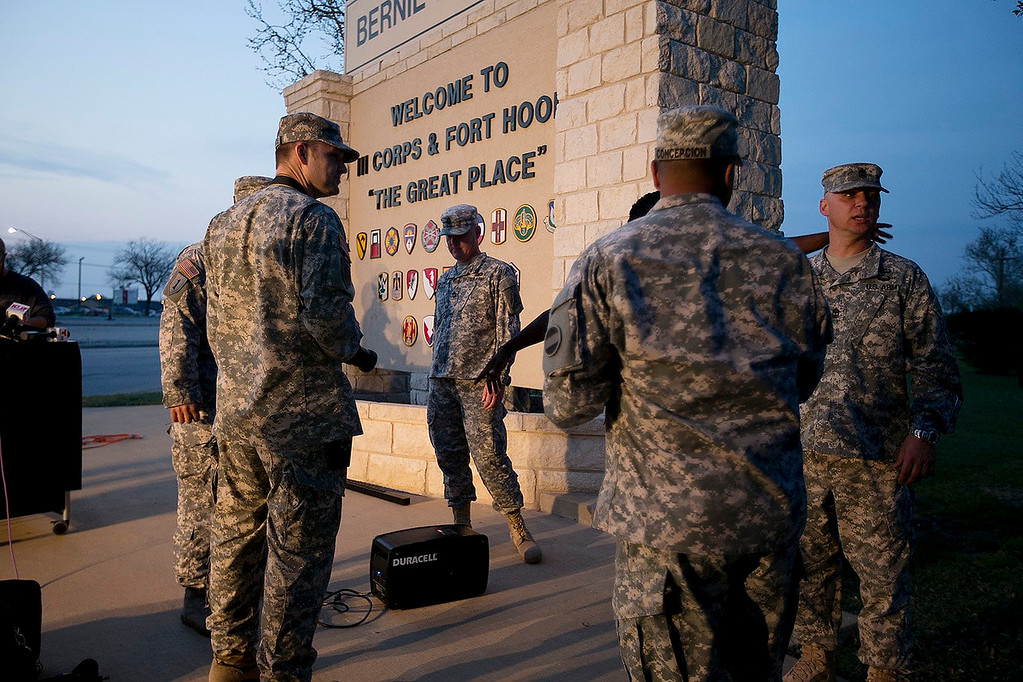 Description of . Military personnel wait for a news conference to begin at Fort Hood, Texas, on Wednesday, April 2, 2014. A gunman opened fire in an attack that left four people killed including the shooter, at the same post where more than a dozen people were killed in a 2009 mass shooting, law enforcement officials said. The gunman died of a self-inflicted gunshot wound, officials said. At least 14 people were hurt in the shooting. (AP Photo/Austin American-Statesman, Deborah Cannon)