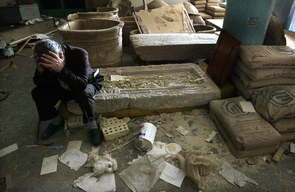 Description of . Iraqi National Museum Deputy Director Mushin Hasan holds his head in his hands as he sits on destroyed artifacts April 13, 2003 in Bagdhad, Iraq. The museum was severely looted in the preceding days. (Photo by Mario Tama/Getty Images)