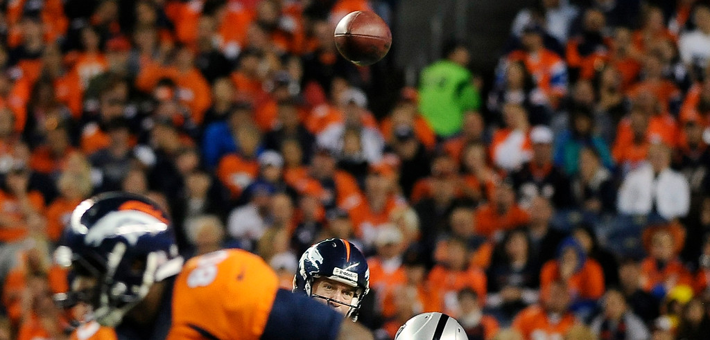 Description of . Denver Broncos quarterback Peyton Manning (18) watches a pass to Eric Decker in the third quarter. The Denver Broncos took on the Oakland Raiders at Sports Authority Field at Mile High in Denver on September 23, 2013. (Photo by Steve Nehf/The Denver Post)
