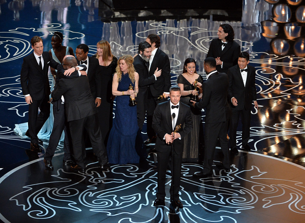 Description of . Actor/producer Brad Pitt (C) accepts the Best Picture award for '12 Years a Slave' with (back row) actors Benedict Cumberbatch, Lupita Nyong'o, Chiwetel Ejiofor, producers Dede Gardner, Jeremy Kleiner and Anthony Katagas onstage during the Oscars at the Dolby Theatre on March 2, 2014 in Hollywood, California.  (Photo by Kevin Winter/Getty Images)
