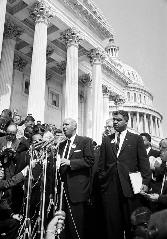 Description of . A. Philip Randolph, head of the  Brotherhood of Sleeping Car Porters, talks to newsmen at the Capitol after leader of the March on Washington met with congressional leaders, Aug. 28, 1963. At right is Whitney Young of the National Urban League. (AP Photo)