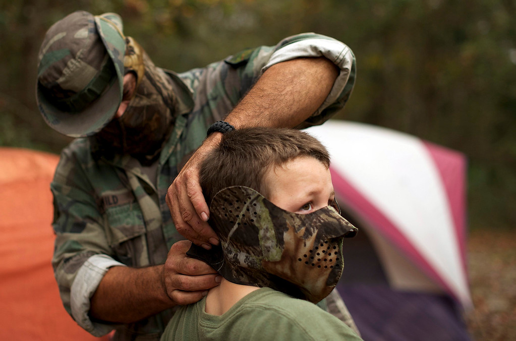 ". A member of the North Florida Survival Group puts a mask on his son as they gear up to perform enemy contact drills in a wooded area during a field training exercise in Old Town, Florida, December 8, 2012. The group trains children and adults alike to handle weapons and survive in the wild. The group passionately supports the right of U.S. citizens to bear arms and its website states that it aims to teach ""patriots to survive in order to protect and defend our Constitution against all enemy threats\"". Picture taken December 8, 2013.   REUTERS/Brian Blanco"