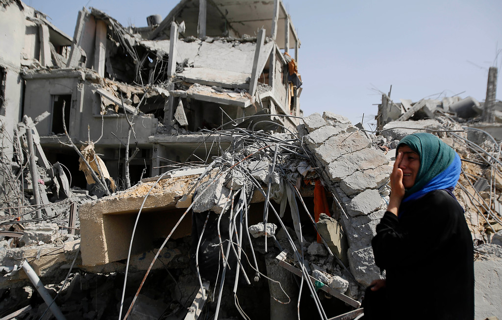Description of . A Palestinian woman cries as she stands near the rubble of her home in Beit Hanoun, Gaza Strip, Friday, Aug. 1, 2014. A three-day Gaza cease-fire that began Friday quickly unraveled, with Israel and Hamas accusing each other of violating the truce. (AP Photo/Hatem Moussa)