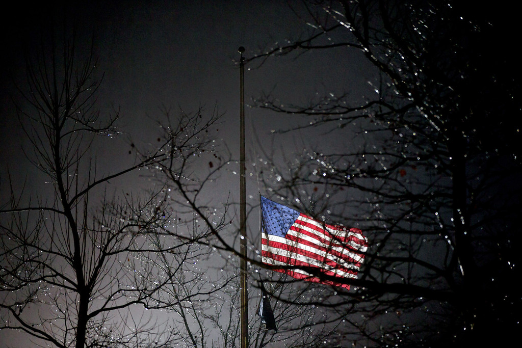 Description of . A U.S. flag flies at half staff outside the  Newtown High School before President Barack Obama is scheduled to attend a memorial for the victims of the Sandy Hook Elementary School shooting, Sunday, Dec. 16, 2012, in Newtown, Conn. A gunman walked into Sandy Hook Elementary School in Newtown Friday and opened fire, killing 26 people, including 20 children. (AP Photo/David Goldman)