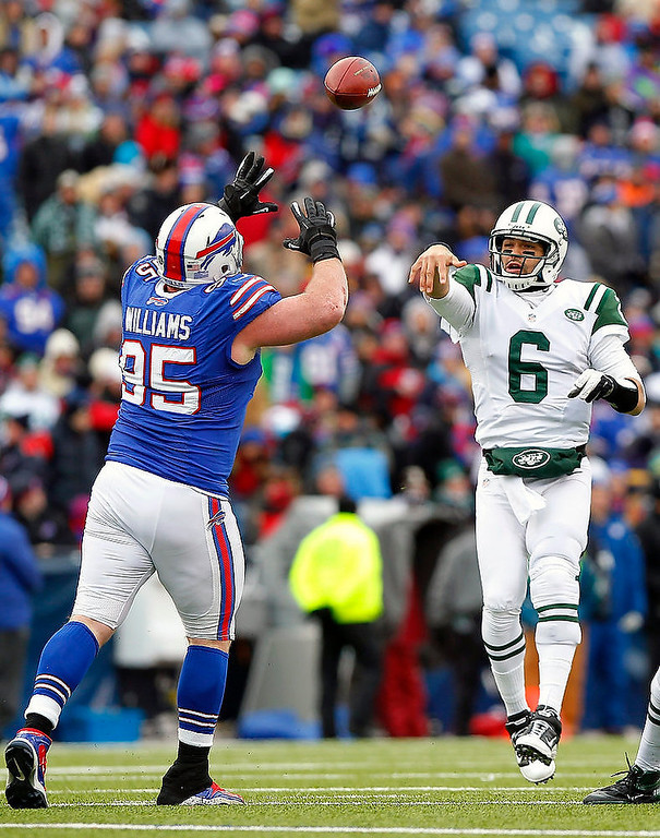 Description of . New York Jets quarterback Mark Sanchez (6) passes under pressure from Buffalo Bills defensive tackle Kyle Williams (95) during the first half of an NFL football game on Sunday, Dec. 30, 2012, in Orchard Park, N.Y. (AP Photo/Bill Wippert)