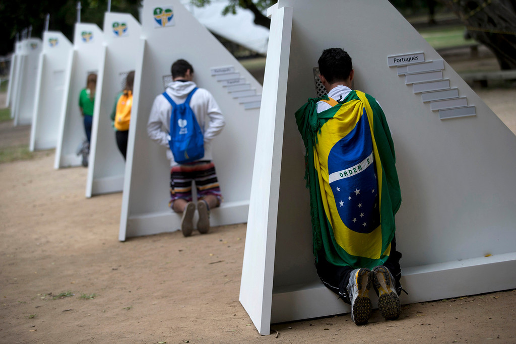 Description of . Catholics kneel at portable confessionals set up in Quinta da Boa Vista park during World Youth Day events in Rio de Janeiro, Brazil, Tuesday, July 23, 2013. As many as 1 million young people from around the world are expected in Rio for the Catholic youth event.  (AP Photo/Silvia Izquierdo)