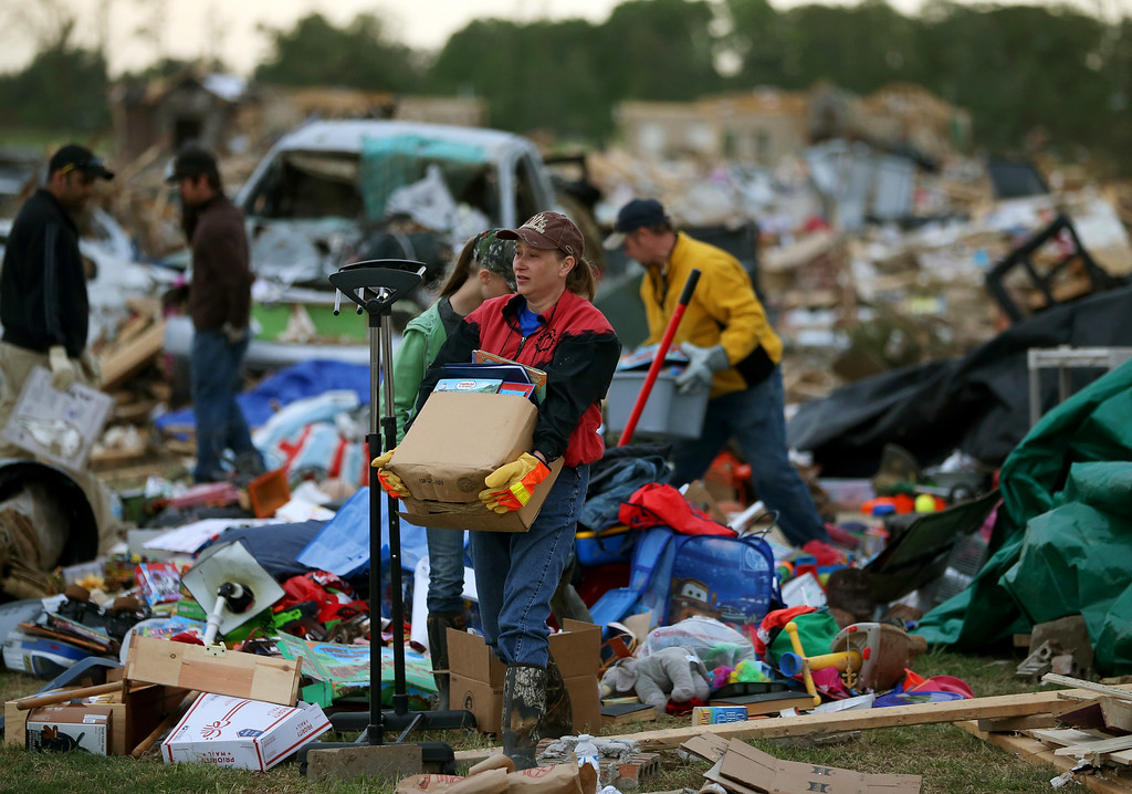Description of . Volunteer Gina Lowe (C) helps a family move belongings from a home that was destroyed by a tornado on Sunday, April 29, 2014 in Vilonia, Arkansas.  (Photo by Mark Wilson/Getty Images)