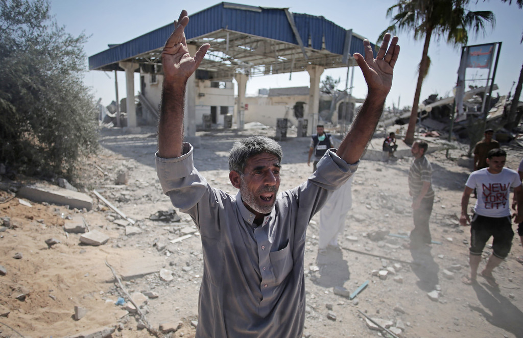 Description of . A Palestinian man reacts after seeing the ruins of houses caused by Israeli strikes in the village of Khuzaa, southern Gaza Strip, close to the Israeli border, Friday, Aug. 1, 2014. A three-day Gaza cease-fire that began Friday quickly unraveled, with Israel and Hamas accusing each other of violating the truce. (AP Photo/Khalil Hamra)