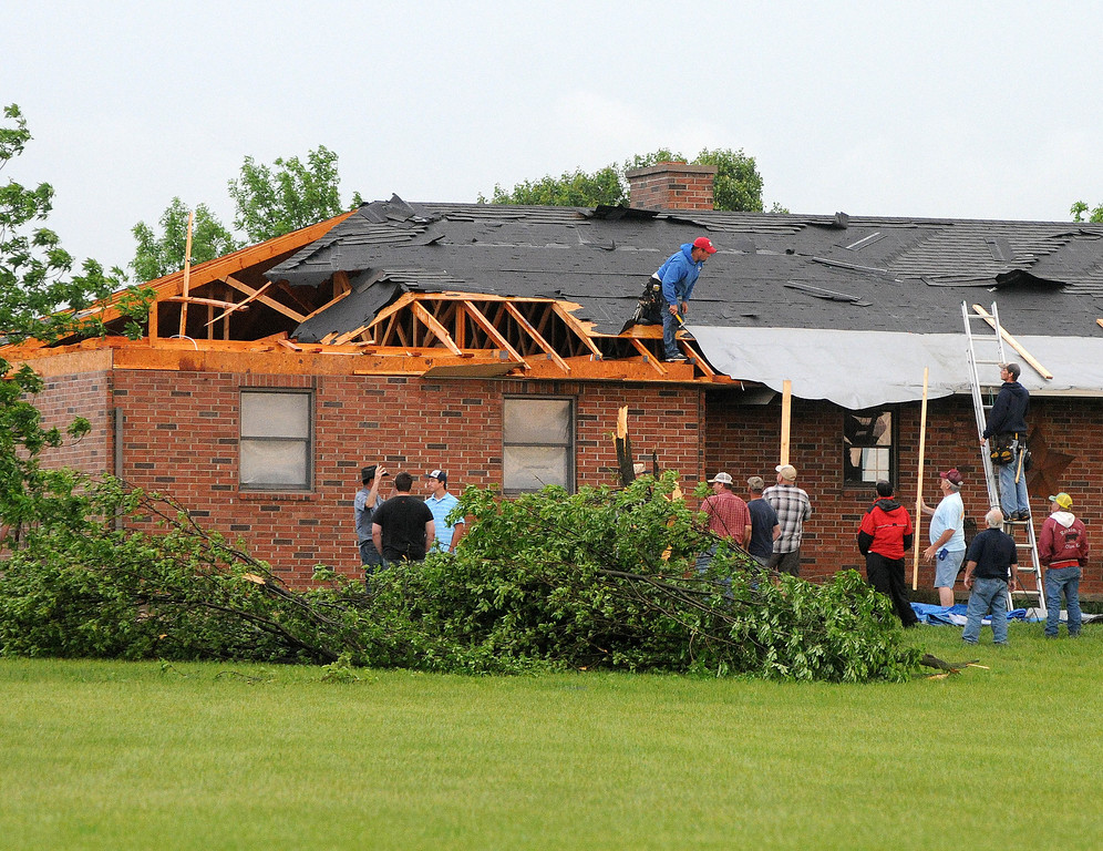 Description of . Friends and neighbors help out a resident in Lyon County just south of Emporia, Kan., Sunday evening, May 19, 2013 after an apparent tornado touched down. (AP Photo/Emporia Gazette, Matthew Fowler)