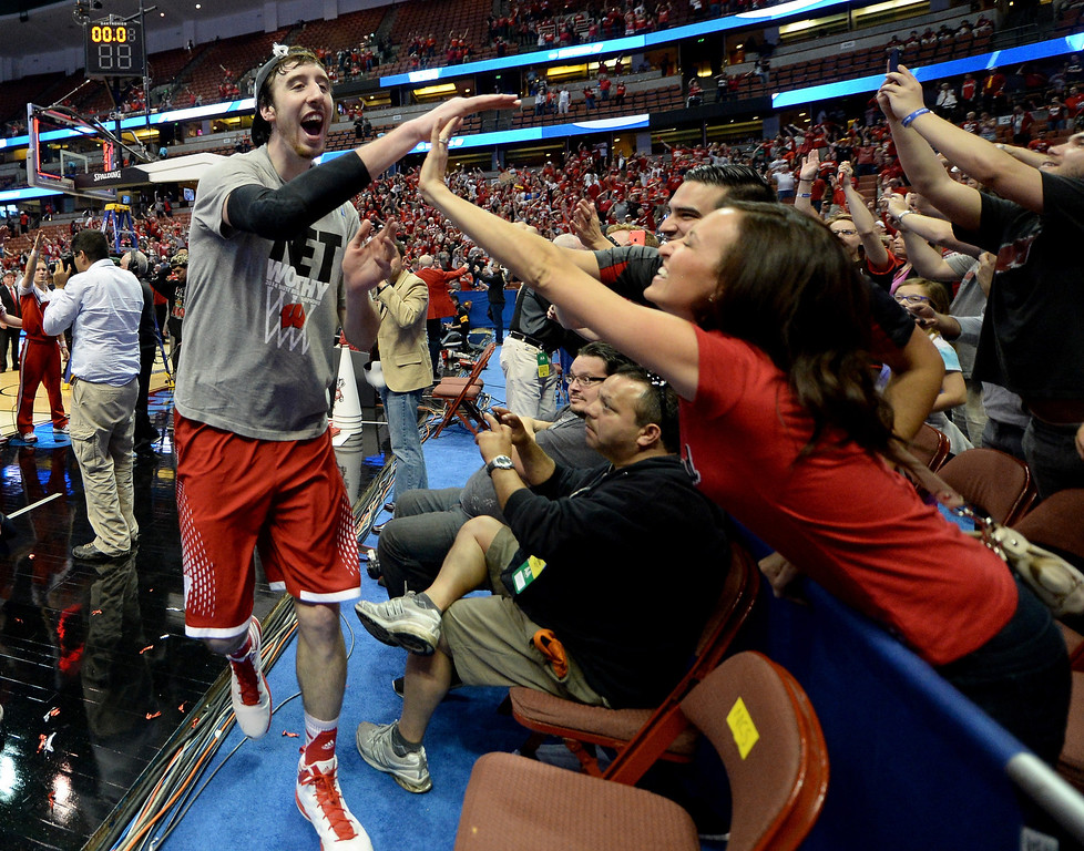 Description of . Frank Kaminsky #44 of the Wisconsin Badgers celebrates with fans defeating the Arizona Wildcats 64-63 in overtime during the West Regional Final of the 2014 NCAA Men's Basketball Tournament at the Honda Center on March 29, 2014 in Anaheim, California.  (Photo by Harry How/Getty Images)
