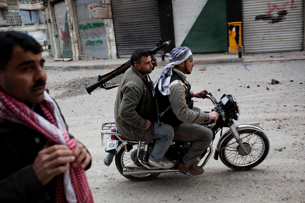 Description of . FILE - Free Syrian Army fighters ride a motorbike to approach Syrian Army tanks in Idlib, north Syria, Sunday, March 11, 2012. (AP Photo/Rodrigo Abd, File)